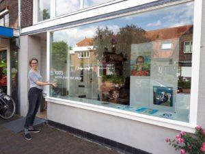 Judy staat naast de galerie waar zij exposeert en wijst naar de titel van de expositie op het raam: Roots. Wortels praten met elkaar.